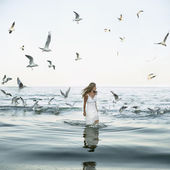 Beautiful woman and seaguls on the beach — Stock Photo