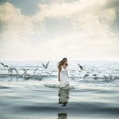 Beautiful woman and seaguls on the beach — Stock Photo