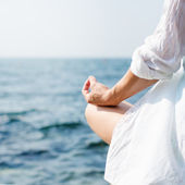 Woman meditating at the sea — Stock Photo