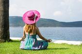 Kobieta siedzi na plaży — Zdjęcie stockowe