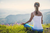 Young woman meditate on the top of mountain — Stock Photo