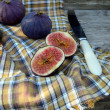 Cuted figs with a knife and tablecloth — Stock Photo