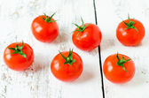 Fresh tomatoes on the wooden background — Stock Photo
