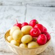 Fresh young potatoes and radishes in a basket - Stock Photo