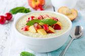 Milk porridge with peaches and cherries — Stock Photo