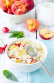Milk porridge with peaches and cherries — Stock Photo