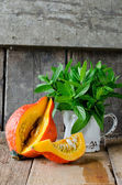 Pumpkin and mint on a wooden table — Stock Photo
