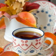 A cup of tea on the table with autumn leaves — Stock Photo