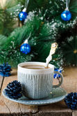 A cup of coffee on a wooden table with Christmas decorations — Stock Photo