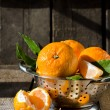 Tangerines in a bowl on a wooden table — Stock Photo