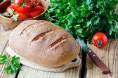 Hembakat bröd på träbord med färska grönsaker — Stockfoto