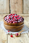 Cranberries in a wooden bowl on a wooden table — Stock Photo