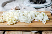 Chopped onion and garlic on a cutting board — Stock Photo