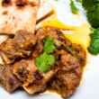 Lamb curry coriander and Naan close up on a white plate - Stock Photo