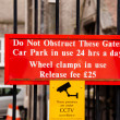 Stock Photo: Warning sign for motorists Do not obstruct these gates, car park in use 24 hours day, wheel clamps in use