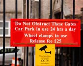 Warning sign for motorists Do not obstruct these gates, car park in use 24 hours a day, wheel clamps in use — Stock Photo