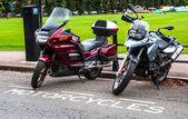 Motocicletas estacionadas na frente de um parque da cidade — Fotografia Stock