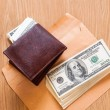 Wallet with money on wooden background and brown envelop — Stock Photo