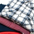 Pile of Shirts and T Shirts in different colors isolated on white — Stock Photo