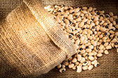 Black eyed peas in jute bag on jute background — Stock Photo