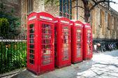 řada vintage britské červené telefonní budky — Stock fotografie