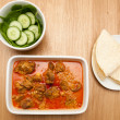 Indian curry lamb rogan josh in a white dish, with naan bread. — Stock Photo #49480183