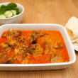 Indian curry lamb rogan josh in a white dish, with naan bread. — Stock Photo #49480247