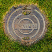 Water Manhole Cover in Grass — Stock Photo