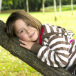 Little girl on a tree branch in the park — Stock Photo