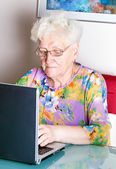 Old woman using computer — Stock Photo