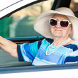 Happy senior woman in sunglasses and hat driving automobile — Stok fotoğraf