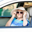 Old woman in sunglasses sitting in the car — Stock Photo