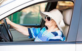 Mature woman in sunglasses driving automobile — Stok fotoğraf
