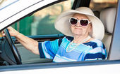 Happy senior woman in sunglasses and hat driving automobile — Stock Photo