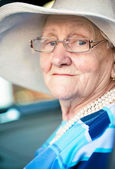 Old woman sitting in automobile — Stock Photo