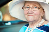Portrait of a mature woman in glasses and hat sitting in car — Stock Photo