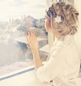 Beatiful girl looking through window — ストック写真