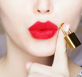 Woman with red lips holding gold lock — Stock Photo