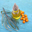Sea ​​buckthorn oil in jar on blue wooden background, close- — Stock Photo #13969418