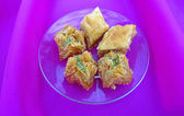 Sweet baklava on saucer on pink tablecloth, close-up — Stock Photo