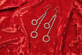 Woman earrings on red velvet background, close-up — Stock Photo
