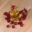 Bottle with oil and dried rosehip berries, close-up — Stock Photo