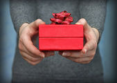 Red gift box in hands, close-up — Stock Photo