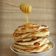 Tasty pancakes with honey and wooden dipper on canvas background — Stock Photo