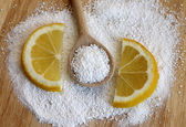 Citric acid in wooden spoon with lemon, close-up — Stock Photo