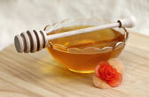 Bowl of honey with wooden drizzler, close-up — Stock Photo
