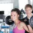 Woman with coach doind exercises with bar — Stock Photo