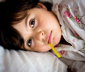 Little girl with thermometer in bed — Stockfoto