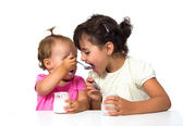 Little girls eating yogurt — Stock Photo