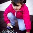 Little girl painting with chalk — Stock Photo